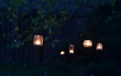 upcycled glass jar garden lanterns hanging from tree branches at night